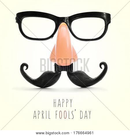 fake eyeglasses, nose and mustache and the text happy april fools day in a beige background, with a retro effect