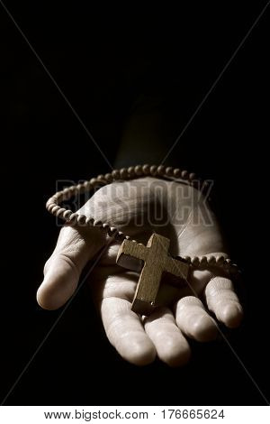 closeup of the hand of a young caucasian man with a rosary with a wooden cross in it