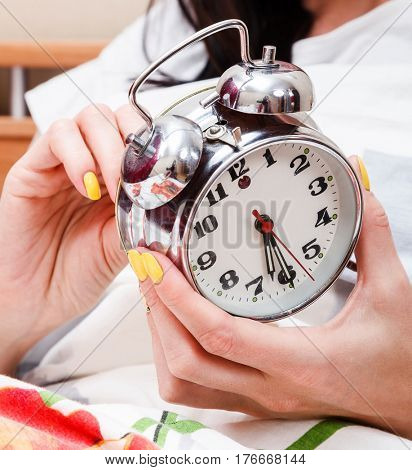 Woman in a bed setting the alarm clock