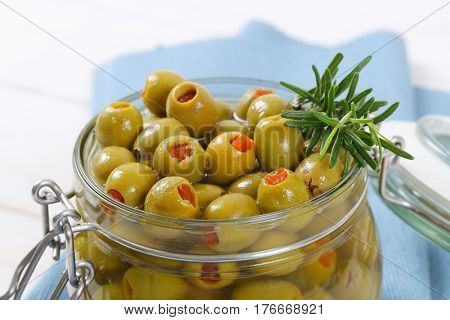 jar of green olives stuffed with red pepper on blue place mat - close up