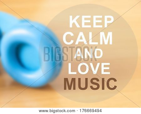 The quot of KEEP CALM AND LOVE MUSIC with blue head phone on wooden background