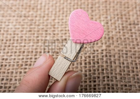 Colorful heart attached to a clothespin in hand