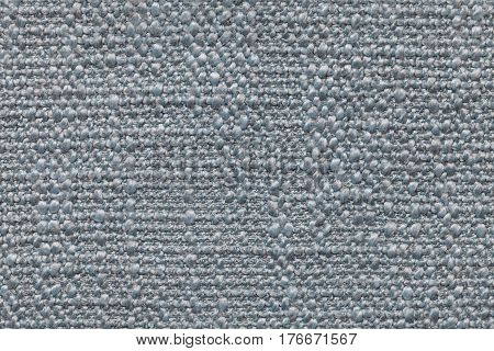 Light blue knitted woolen background with a pattern of soft fleecy cloth. Texture of textile closeup.