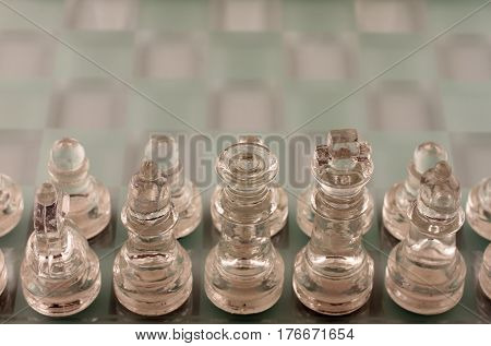 Glass Chess Pieces Lined Up for Battle