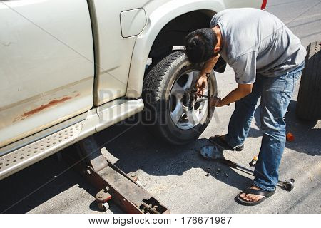 A Man Changing The Wheel At The Side Of The Road