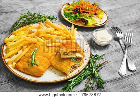 Lunch from fish in breadcrumbs and dough french fries potatoes fresh lettuce salad leaves. Tartar sauce for fish. Greens for French fries thyme rosemary. Light white wooden background.