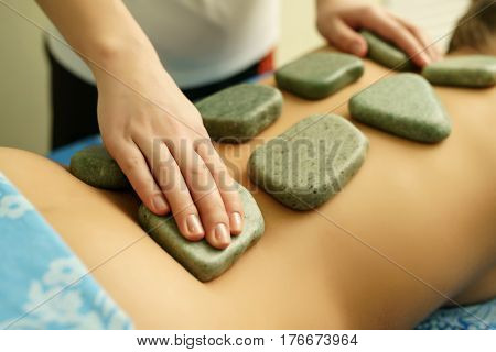 Young woman getting pleasure while lying on the stomach and receiving hot basalt stone massage in spa center. Beauty treatment concept, close-up, selective focus, shallow depth of field