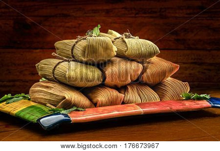 Tamales Mexican dish made with corn dough chicken or pork and chili wrapped with a corn leaf