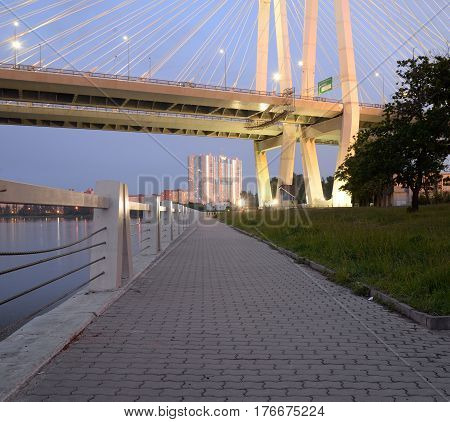 Cable stayed bridge and embankment of Neva river on the outskirts of St. Petersburg at evening Russia.