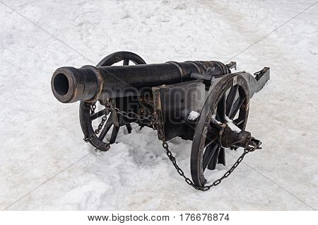 Ancient cannon in castle Palanok of Mukachevo Ukraine. Winter time white snow background.