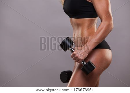 closeup body of fitness woman with dumbbells . Sporty girl showing her well trained body . isolated on grey background with copyspace.