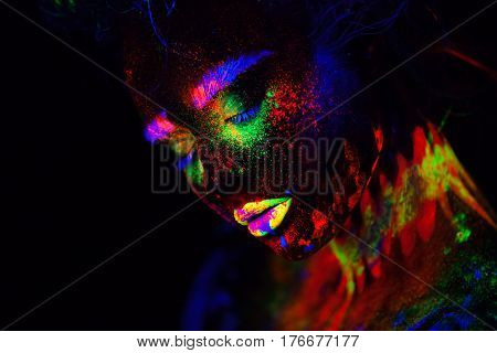 Close up beautiful extraterrestrial model woman in neon light. It is portrait of beautiful model with fluorescent make-up, Art design of female posing in UV with colorful make up. Isolated on black background