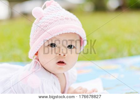 Cute Asian Baby Lie Prone On Ground At Park