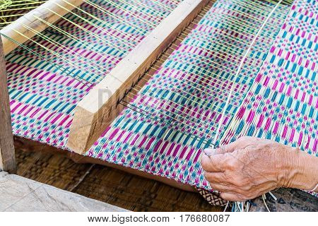 Old woman hand is reed weaving mats in closeup