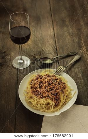 A photo of a plate of pasta with meat and tomato sauce, with a glass of red wine and a place for text