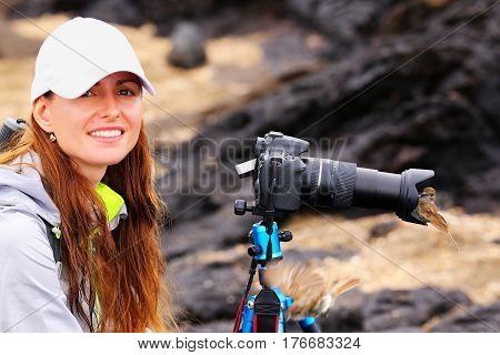 Young woman photographing on Santiago Island with Galapagos flycatcher on her lens hood Galapagos National Park Ecuador