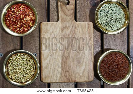 Bowls of spices containing mustard seeds fennel seeds coriander seeds red pepper flakes on a wooden background sith copy space.Top view.