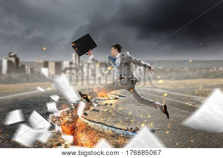 Businessman trying to overcome deep break . Mixed media
