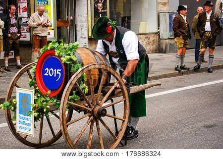 Munich,Germany-September 19,2015: A man with a wooden beer barrel on wheel barrow gets ready for the brewers parade at the start of th Oktoberfest