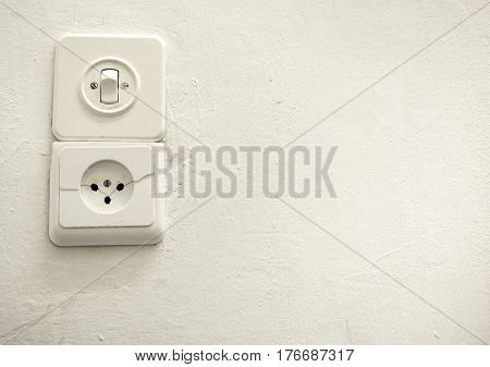 Old vintage switch and socket on a white plastered wall