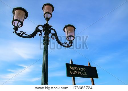 Gondola service sign and street lamp against blue sky near Piazza San Marco in Venice Italy. For centuries the gondola was the chief means of transportation and most common watercraft within Venice