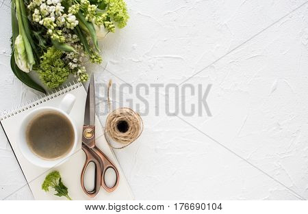 Feminine flatlay with flowers and ccoffee on white textured tabletop, design ready arrangement