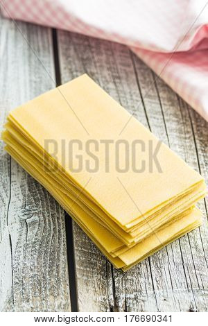 Raw lasagne sheets on old wooden table.