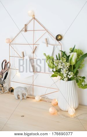 Feminine hipster office table decoration with flowers and mood board on white wall, woman's workplace