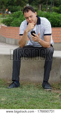 Man Thinking Using Cell Phone Sitting on Wall