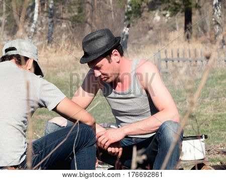 Traveling - young Man in hat in camping playing chess, horizontal