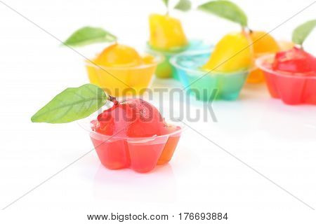 Red deletable imitation fruits in jelly cup on white floor.