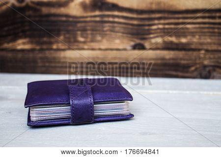 violet leather card holder on wooden background