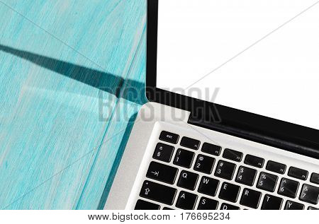 Modern laptop computer on blue wooden table with blank screen close-up