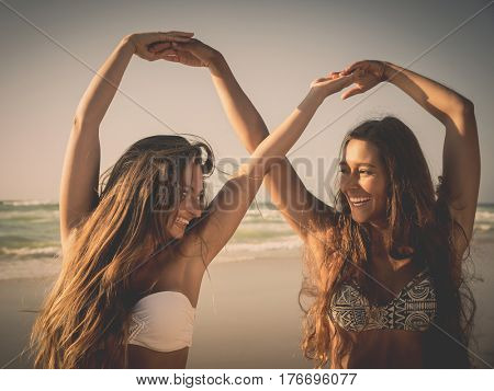 Beautiful girls in the beach giving her hands together