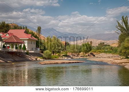 Houses standing in a valley of a mountain river surrounded by mountains
