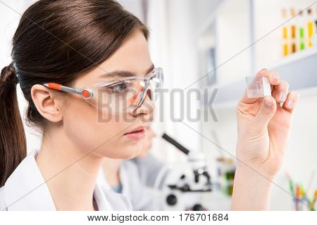 Young female scientist in protective eyewear holding glass microscope slide in laboratory