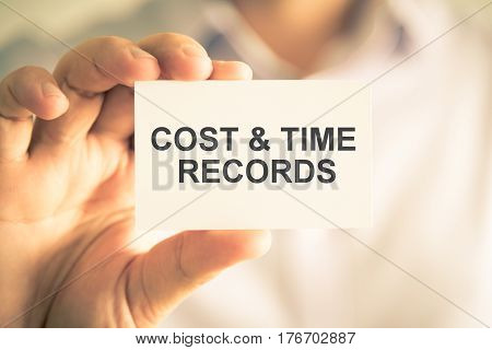 Businessman Holding Cost And Time Records Message Card