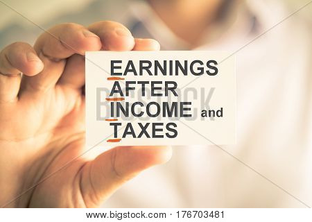 Businessman Holding Card With Eait Earnings After Income And Taxes Acronym Text