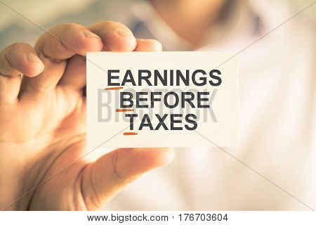 Businessman Holding Card With Ebt Earnings Before Taxes Acronym Text
