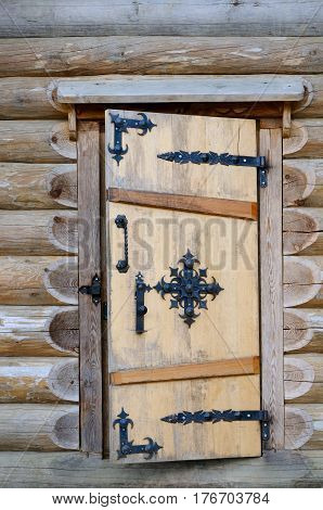 The door in log house with wrought-iron hinges