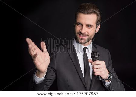 Young friendly man talking in microphone and gesticulating on black