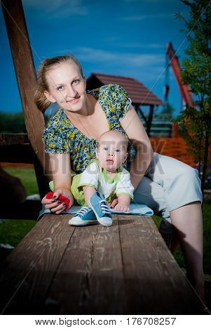 Beautiful Mother And Baby outdoors. Nature. Beauty Mum and her Child playing in Park together. Outdoor Portrait of happy family. Joy. Mom and Baby