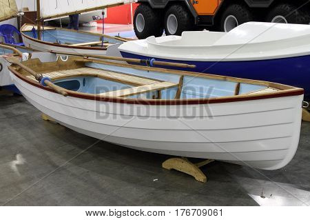 Modern white boat with oars stowed along the side
