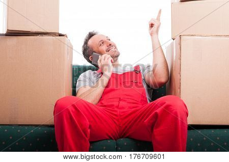 Mover Man Sitting On Couch Talking At Phone