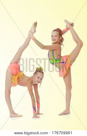 Two adorable little twin girls, gymnastics in the sports school. Girls beautiful gymnastic leotards. They do the splits.On a yellow gradient background.