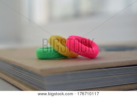 Colorful scrunchies (green yellow red) on book background