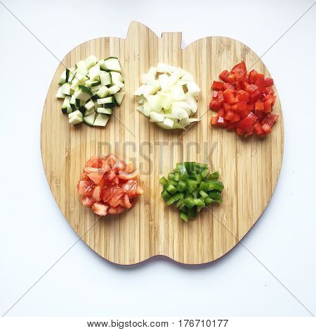 Diced Vegetables on cutting board on white background top view