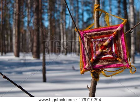 Colorfull indian dreamcatcher in Siberian forest. Central Siberian Botanical Garden Akademgorodok Novosibirsk Russia. March 2017.