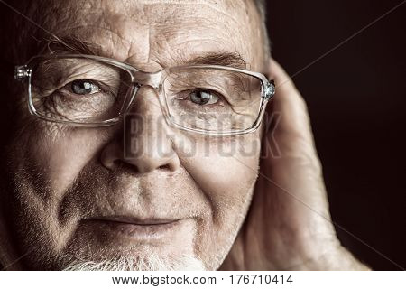 Portrait of a smiling old man over black background. Old age concept.