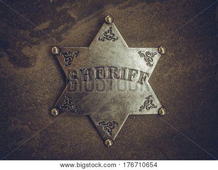 Sheriff badge on natural stone background. Macro shot.